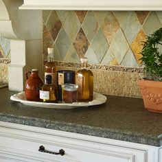 Layered Look Backsplash. Yellow limestone mosaic tiles form the base of the backsplash in this European-inspired kitchen. The bronze liner bar above them complements the copper range hood while slate tile in a romantic harlequin pattern adds subtle color. Kitchen Backsplash Photos, Beadboard Backsplash, Herringbone Backsplash, Backsplash Design, Backsplash Ideas, Tile Ideas, Rock Backsplash, Kitchen Redo, Kitchen Design