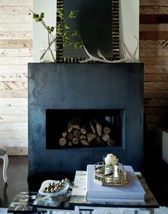 Steel fireplace with rivet details, mosaic tile at firebox opening, simple mantel, wood walls, concrete floors - Jamie Laubhan-Oliver