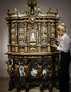 Alexandra Robinson stands next to a 17th century Louis XIV cabinet-on-stand, make by Italian furniture master Domenico Cucci, on display at the auction house in London.