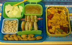 Kids Bento Box Lunch. Apples, Cherrios, Cinnamon apple sauce, almonds, little pepperoni sandwiches. Side tin of gold fish