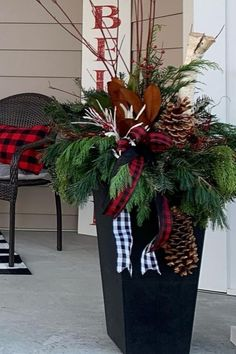 """Lush winter greenery is tucked with natural pinecones and curly willow, and layers of buffalo plaid ribbon! Great winter planter design by Tara Mayoros, a talented container designer in Utah! The 36"""" Sonata is made of recycled rubber from used car tires diverted from landfill. This eco-friendly planter is naturally black and looks great with the color choices by Tara, for this lucky client to match her front door decor plan! Winter Planter, Curly Willow, Rubber Material, Recycled Rubber, Front Door Decor, Buffalo Plaid, Timeless Design, Utah, Greenery"""