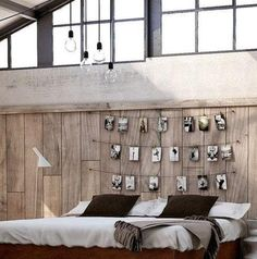 Bedroom in a converted warehouse. Big windows and black-and-white photographs on a string.