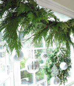 kitchen cedar garland strung over bay window, hang silver ornaments behind so they catch the light.