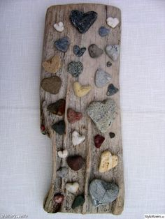 heart-shaped pebbles on a piece of weathered wood.