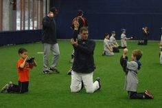 Chris Ledbetter, head baseball coach at Oak Park-River Forest High School, helps two young ballplayers with a throwing drill during a baseball camp at the Bounce Sports Sportsplex in Berwyn. (Staff photo by Matthew Piechalak)