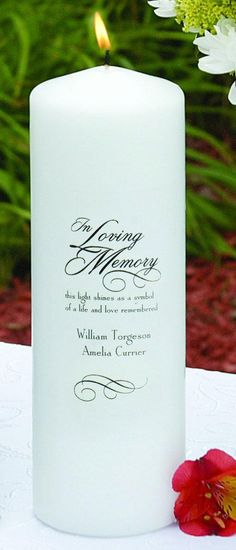 """""""In Loving Memory"""" Memorial Candle made of white wax. The front of the candle is printed with phrase """"In Loving Memory"""" with a swirl accent. It is followed by the phrase """"this light shines as a symbol of a life and love remembered"""". The bottom is printed with another swirl accent.  This item can be personalized."""