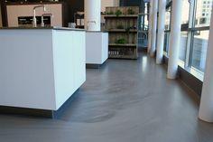 Betonlook pu gietvloer met strakke meubels zorgen voor eenheid in
