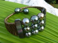 Island cuff ,selected tahitian pearls , mother of shell spacers and metal bronze leather braided over memory wire.  www.facebook.com/blackmarketpearls