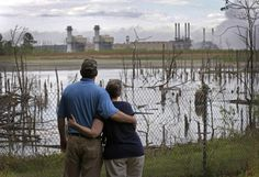 In this April 25, 2014 photo, Bryant Gobble, left, hugs his wife, Sherry Gobble, right, as they look from their yard across an ash pond full of dead trees toward Duke Energy's Buck Steam Station in Dukeville, N.C.