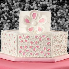 Soft rose petal pink color peeks through the floral petal cutaways to present a wedding cake that is both fun and charming. Color Flow icing makes the horizontal panels and the flower topper.