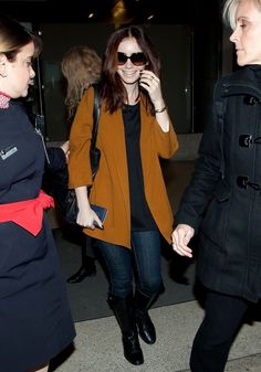 Lily Collins airport style: Zara wool coat, long top, dark wash denim jeans, knee high boots, casual hair & sunglasses