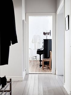 An serene hallway and black piano in a Swedish home in perfect harmony