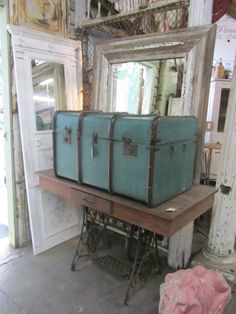 Table, trunk, mirror and door. That blue trunk is wonderful. From the My Country Roads blogspot.