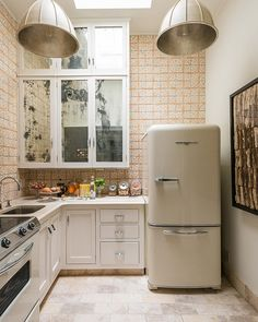 The vintage feel of this kitchen was preserved thanks in large part to the '50s style refrigerator, while Mediterranean tile lines the walls. Mercury-glass mirrors were added to the cabinet doors in order to brighten the tiny space.