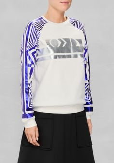 SADIE WILLIAMS & OTHER STORIES A classic raglan-sleeve sweater in off-white is turned into a bold sporty-chic statement with chunky metallic prints allover the sleeves and at front.