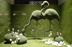 """Hermès has enlisted several international designers to create window displays for their Spring lines. Nendo envisioned a """"wandering forest"""" concept with minimal tree branches holding hats and scarves; Eindhoven-based Kiki van Eijk created Alice in Wonderland-like scenes with watercolor; and lush green animals display the company's wares in Paris."""