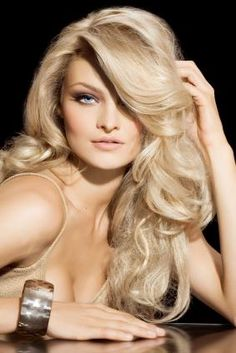 Long Wavy Curls  Parted deeply on the side, this style features long, luscious curls with plenty of volume. After using a curling iron, apply gloss to attain this look