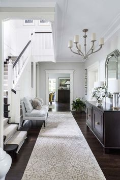 Open entryway with dark accents and a long hallway, making the space feel spacious and airy. Interior Design - Coco Republic - North Shore Residence, NSW