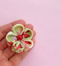 A pastel flower lapel pin boutonniere for men and women, made in the Japanese tsumami kanzashi style! This attention-grabbing pin is a unique fashion accessory no one else can own. I used a Japanese green chirimen silk with red, pink, brown, cream and white for this kanzashi flower. I sewed a coral bead into the center and mounted everything on a tie tack with a butterfly clutch back. Complements a suit, blazer, cardigan, hat, or sports jacket. The modeled photo is an earlier version of the…