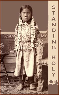 """Standing Holy was born to Sitting Bull's fifth wife, her name was Seen by Her Nation. She was the sister of Grey Eagle. Standing Holy was born 1878 and died in 1920. She was married twice. Firstly to  Urban Spotted Horse then in 1915 married John Black Wolf. I added the text and border because of the condition of the original but the original was the best photo of her I've found so far."""