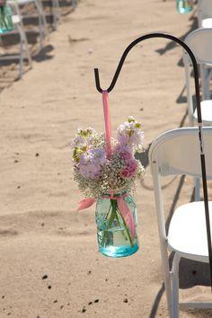 light blue tinted mason jars with light pink flowers hanging down the aisle #wedding #masonjars #floral