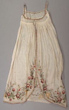"""Overdress ca. 1800–1810. Sheer Cotton; Wool Embroidery. French. Overdress of natural sheer cotton with polychromatic wool embroidery: very narrow bodice (2.5""""); straight drawstring neckline closure at center front; narrow band of embroidery along neckline and shoulder; evidence that sleeves may have been removed from band at shoulder; center front opening skirt gathered into empire line waistband; narrow band of embroidery along sloped skirt hem. Fine arts museums of San Francisco:"""