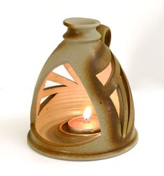 Something like this. One piece with stable base. Easy access to candle, which is also stabilized. Attached handle.