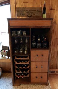 Antique wardrobe repurposed as a liquor cabinet.