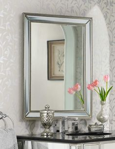 Beaded framed silver wall mirror on wallpapered wall with flowers at @lampsplus