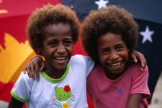 Two young girls from Madang in front of the PNG flag.    Photo by Jerry Galea for Lonely Planet, 2011