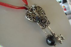 """Filigree Heart with a Large Key, Rose black beads and a Crystal dangling from it. Hangs on a Red Organza Ribbon that measures 18"""" in length with a 1"""" extender"""