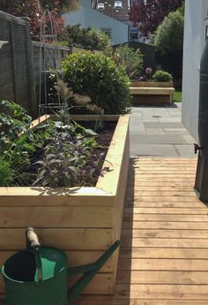 Raised timber vegetable beds in a Brighton garden. In the background an L-shaped fixed bench is set within a grey stone courtyard area