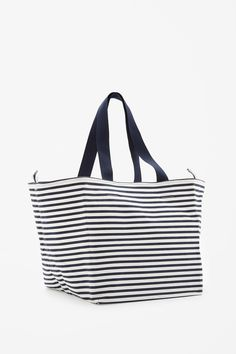 24 This handy bag is made from cotton canvas with an all-over striped pattern and large, unlined interior. Secured with a press stud fastening, it has a smaller inside pocket and comfortable grosgrain strap. Fold it flat for easy travel.