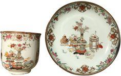 Tasse à décor des cents antiquités en porcelaine de Chine d'époque Yongzheng Tasse et sa soucoupe, peints dans des émaux délicats et très variés de la famille rose d'époque Yongzheng, décorés au centre d'un ensemble de vases archaïques avec des fleurs et fruits, des objets de lettré dit « Bai gu » (cent antiquités). Sur l'aile, un décor de lambrequins et de guirlandes de fleurs.