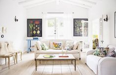 Bright Swedish living space with two neutral sofas and colorful printed throw pillows