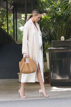 Chrissy Teigen - The expectant mom focused on a neutral palette in cream and beige while out with husband John Legend in Los Angeles this weekend. The vertical stripes on her coat by The Row created an elegant, elongating effect; picking up on the sandy shades were strappy Saint Laurent sandals and a coordinating shoulder bag from The Row.