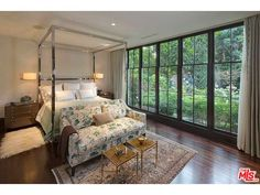 Windows line the wall of this master bedroom, revealing the gorgeous green outdoor scenery you can admire from bed.