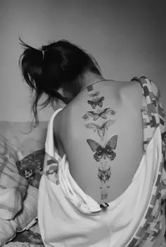 Black flying butterfly tattoo on back body