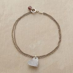"""SLIDING HEART BRACELET--Two delicate chains keep a heart secure while giving it the freedom to slide back and forth. Handmade in France of sterling silver. Bead and spring-ring clasp. 6-3/4""""L."""