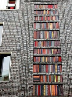 "A ""bookcase"" made out of tiles on the wall of an Amsterdam building."