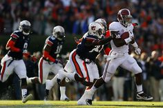 T.J. Yeldon #4 of the Alabama Crimson Tide runs the ball against the defense of Robenson Therezie #27 and Chris Davis #11 of the Auburn Tigers in the first quarter at Jordan-Hare Stadium on November 30, 2013 in Auburn, Alabama.