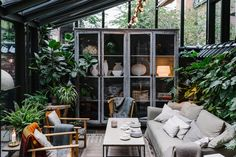 Shown here is the lounge seating vignette in the covered patio/garden area, which is filled with greenery and furniture that's covered with warm textiles.