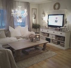 Coffee table, storage cabinet under tv, comfy pillows, white Roman shades and sheer grey curtains