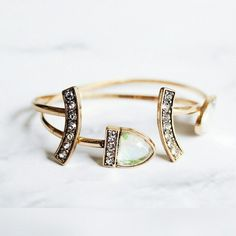 """Stackable opal bundle 2 ultra-chic cuffs. Modern, geometric shapes create a shimmering opalescent arm party + sparkling crystal pave, complete with a versatile antique gold plating. Style this dynamic duo 1 by 1, together side-by-side, or stacked with more // 2.25"""" approx. inner diameter // Multi color opalescent stones on open cuff. Stone color varies from clear to green to lavender (see last photo for examples).  Can be purchased separately for $14 ea. Price is firm. Please do not repost…"""