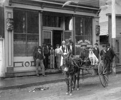 Street scene in front of Georgetown, Colorado saloon. Chan Gow, a Chinese man, sits in a two wheel cart being drawn by a burro.Between 1875 and 1892.