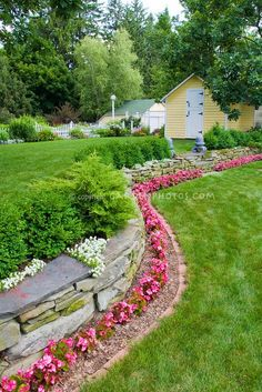 Stone wall with pink flowering wax begonias, Iberis atop stone wall, evergreen shrubs, Buxus boxwood, white picket fence, garden shed, bird house, garage, neat brick edging next to nice lawn grass, steps to tiered two level landscaping, dealing with a slope in the backyard landscape