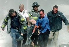 Rescue workers carry fatally injured New York City Fire Department chaplain, the Rev. Mychal Judge, from the wreckage of the World Trade Center in New York City early September 11, 2001. Chaplain was crushed to death by falling debris while giving a man last rites in the trade center.    ★ Credit: REUTERS/Shannon Stapleton  PM