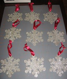 Easy Homemade Ornament snowflakes cut out onto hard cardboard, paint white, and cover with glitter