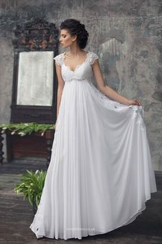 An elegant a-line dress in empire style with a decorated lace keyhole back bodice and a falling chiffon skirt. It's a empire gown where the cap sleeves bodice ends at the lower bust.The embroidery with crystals is a great addition to this model. Dress fully lined with soft gentle to skin material.  <br>This summer wedding dress is very light and comfortable.