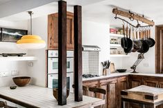 The central feature of the kitchen is a white-tiled work surface that extends from the wall, held by two raw wood beams that extend from the ceiling. It functions as a daily use dining table with four vintage stools perched around it.